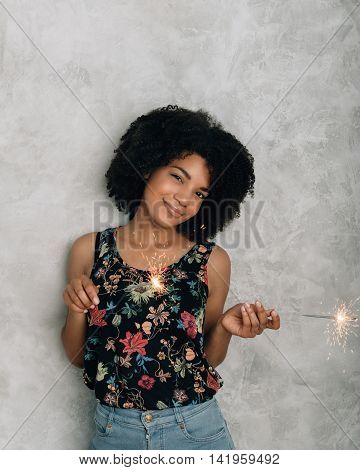 African American young woman playing with sparklers at gray background