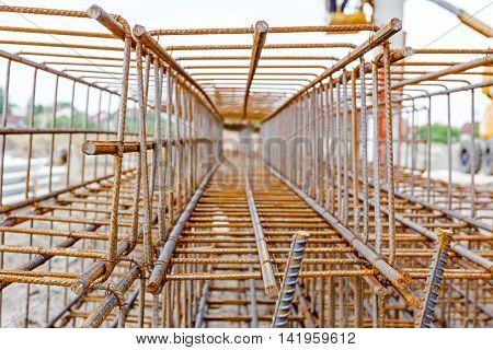 View perspective trough cage skeleton of reinforcing steel bar at construction site.