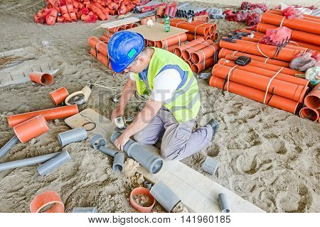 Zrenjanin Vojvodina Serbia - May 21 2015: Rigger is adjusting PVC pipes with grinding machine to correct pipe measure to fit in.