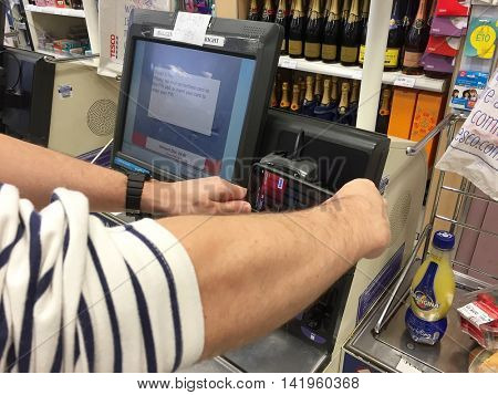 LONDON - AUGUST 9: A shopper uses Apple Pay on an iPhone 6 using an HSBC Debit Card to pay for a lunch meal deal in Tesco Hampstead on August 9, 2016 in London, UK.