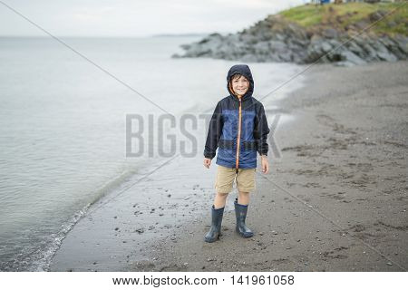 A boy enjoying the rain and having fun outside on the beach on a gray rainy