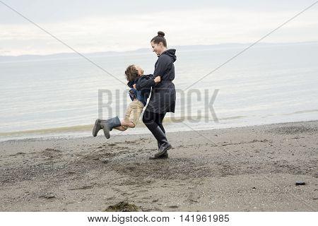 Family two enjoying the rain and having fun outside on the beach on a gray rainy