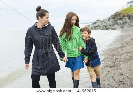 Family of three enjoying the rain and having fun outside on the beach on a gray rainy