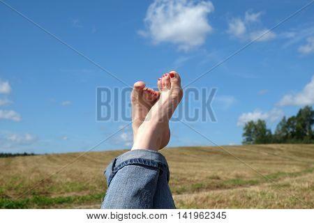 Beautiful playful female bare feet with red nails in rolled blue jeans close-up against summer nature landscape with meadow, sky and country road