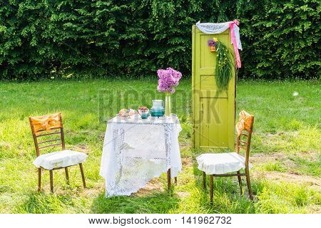Decorated door, table, chairs in the garden