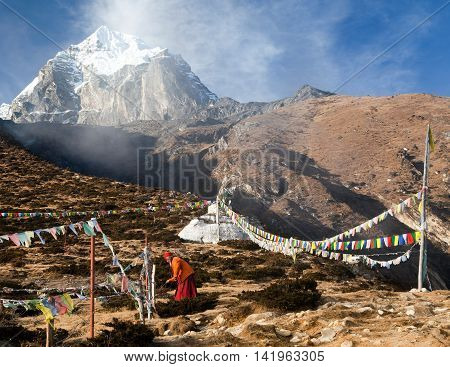 KHUMBU VALLEY NEPAL - 8th NOVEMBER 2014 - Buddhist monk stupa and prayer flags near Pangboche monastery and Tabuche peak life in Khumbu valley on the way to Everest base camp