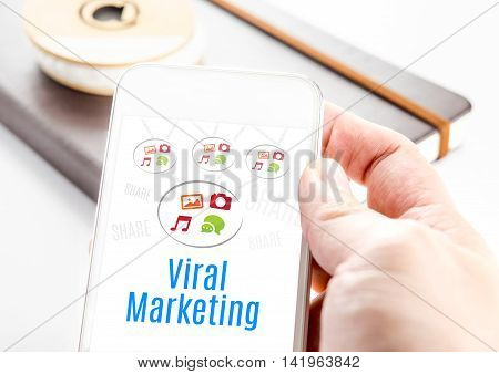 Close Up Hand Holding Smart Phone With Viral Marketing Word And Icons With Notebook At Background, M