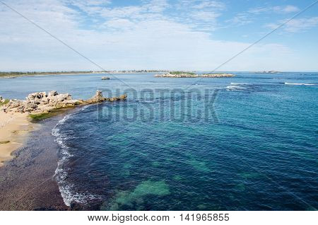 Elevated view of the turquoise-green Indian Ocean waters with limestone outcropping under a blue sky with clouds at Point Peron in Rockingham, Western Australia