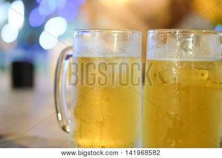 Two glass of beer against barrels at party
