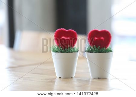 Flowerpot with artificial heart placed on table in concept of marriage and love.