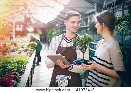 Cheerful male gardener using tablet and talking with young woman holding bonsai tree in pot in orangery