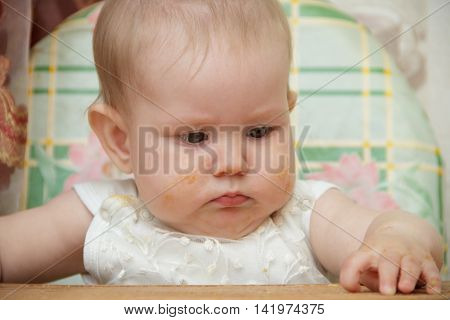 Little child girl sits in a highchair in the kitchen and eats