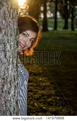 Young brunette woman is popping out behind the tree by sunset. Beauty fashion and nature. Female portrait. Backlight scene. Vertical composition.