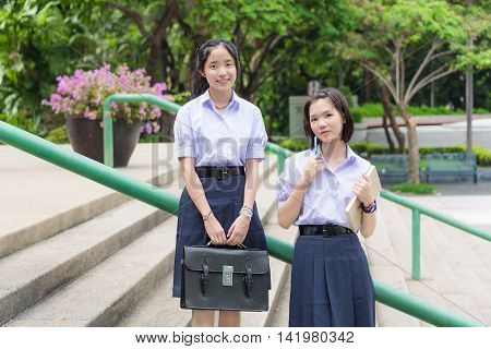 Cute Asian Thai high schoolgirls student couple in school uniform standing on the stairways with her friend looking toward in nature green background
