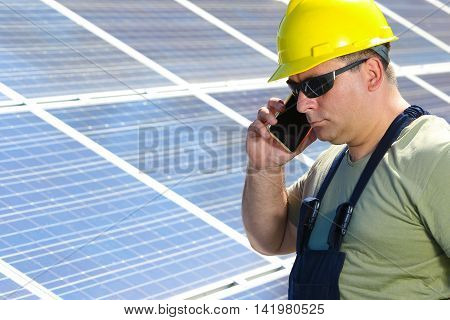Green energy solar panel and worker with cell phone
