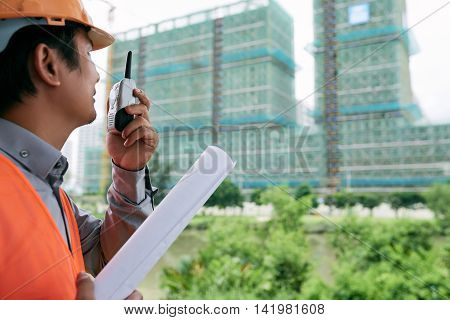 Construction worker using walkie-talkie to communicate with his team