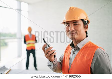Portrait of smiling Vietnamese contractor with walkie-talkie in his hands