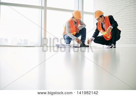 Construction worker and engineer discussing plan of the building