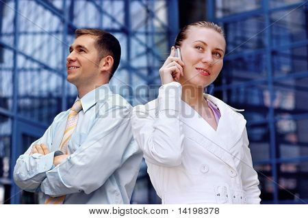 Business women in white and man on business architecture background