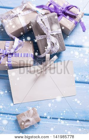 Christmas background. Gift boxes with presents and empty tag on blue wooden background with snow effect. Selective focus. Place for text.