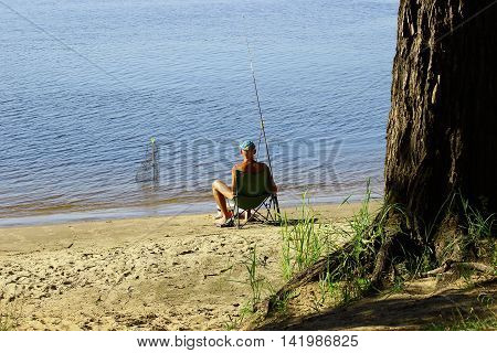 fisherman on a hot Sunny day sitting on the sandy shore and catches the feeder fish. His attention is wholly absorbed in the process of fishing and not notice anything around
