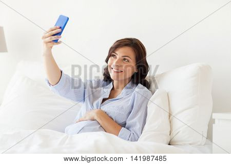 pregnancy, motherhood, technology, people and expectation concept - happy pregnant woman with smartphone taking selfie in bed at home