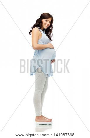 pregnancy, health care and people concept - happy pregnant woman measuring weight on scales over white background