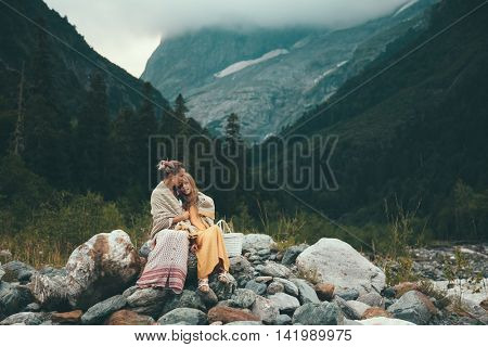 Mom with daughter wrapped in warm blanket outdoor, hiking in mountains, bad cold weather with fog