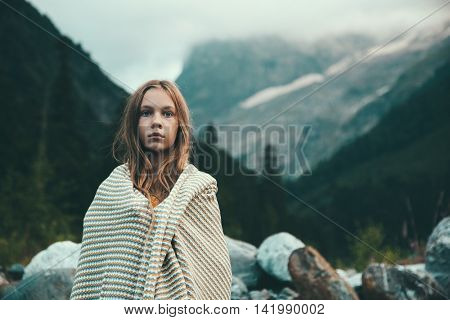 Girl wrapping in warm blanket outdoor, hiking in mountains, bad cold weather with fog