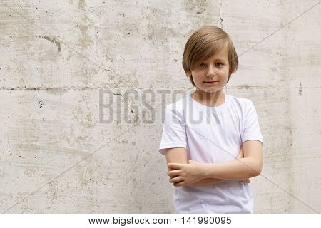 cute blond boy in jeans and a white shirt posing on wall background