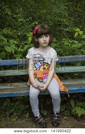 little girl sitting at the wooden banch in the forest