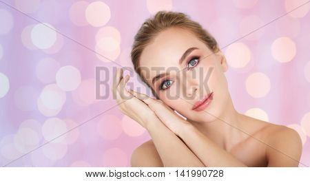 beauty, people and bodycare concept -beautiful young woman face and hands over rose quartz and serenity lights background