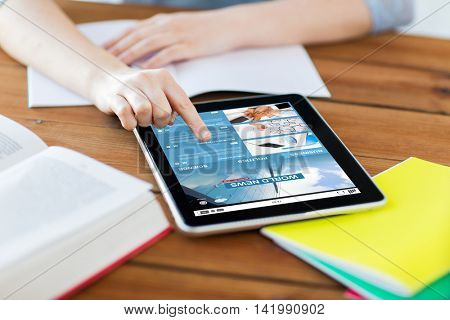 business, education, technology and internet concept - close up of student woman with internet news application on tablet pc computer screen and notebook at home