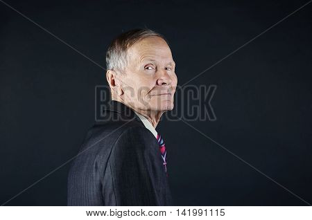 Businessman looking over shoulder on black background with empty copy space