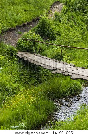 the wooden footbridge under the small river
