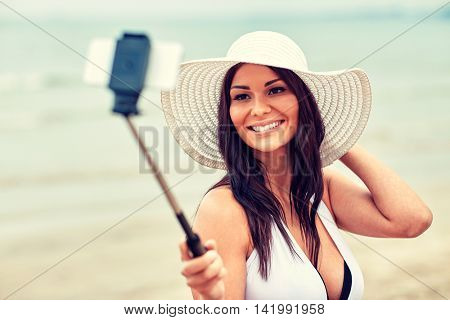 lifestyle, leisure, summer, technology and people concept - smiling young woman or teenage girl in sun hat taking picture with smartphone on selfie stick at beach