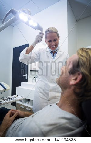 Female dentist interacting with male patient in dental clinic