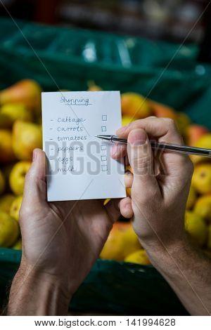 Man ticking on shopping checklist in supermarket