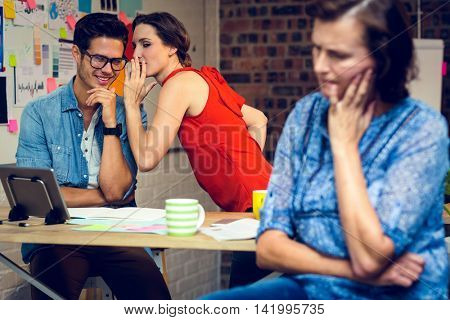 Businesswoman in deep thought and colleagues whispering in background at office
