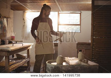 Male potter holding pottery wheel in pottery workshop