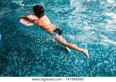 little asian boy with swimming suit in the pool