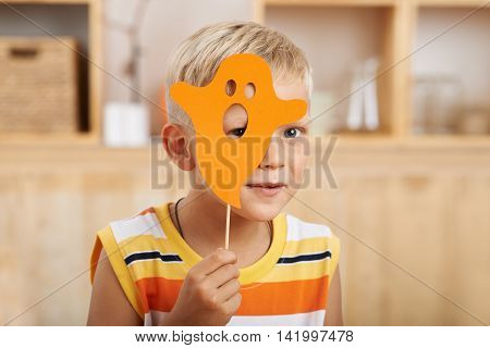 Little boy hiding behind orange paper ghost