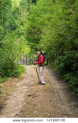 Male hiker with big green traveling rucksack and trekking pole moving up on the mountain trail and smiling happy traveler overcome big way smiling looking away adventure travel and discovery