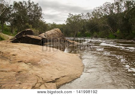 Large rock formations downstream at the Bell Rapids with lush riverbanks under an overcast sky in the Swan Valley in Western Australia.