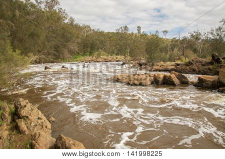 Bell Rapids rocky white waters where the Swan and Avon River intersect in the Swan Valley under a cloudy sky in Western Australia.