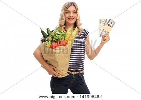 Smiling woman holding a bag of groceries in one hand and stacks of money in the other isolated on white background