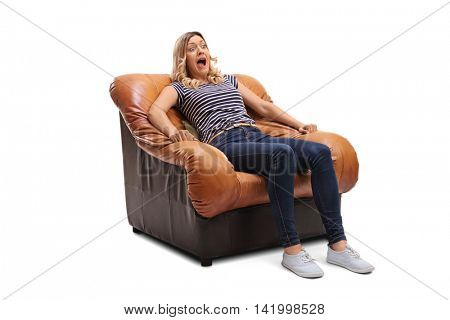 Terrified young woman watching something scary on TV seated on an armchair isolated on white background