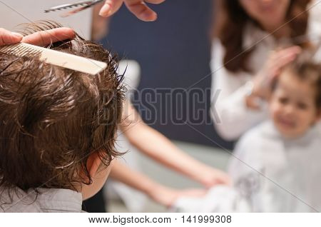 Little boy at hairdresser. Focus on back of the head blurred mirror reflection