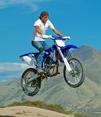 foto of dirt-bike  - Man on blue motorcycle jumping over hill.