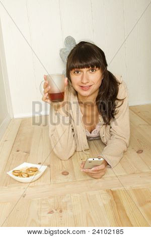 Young Woman With Tea And Mobile Phones At Home